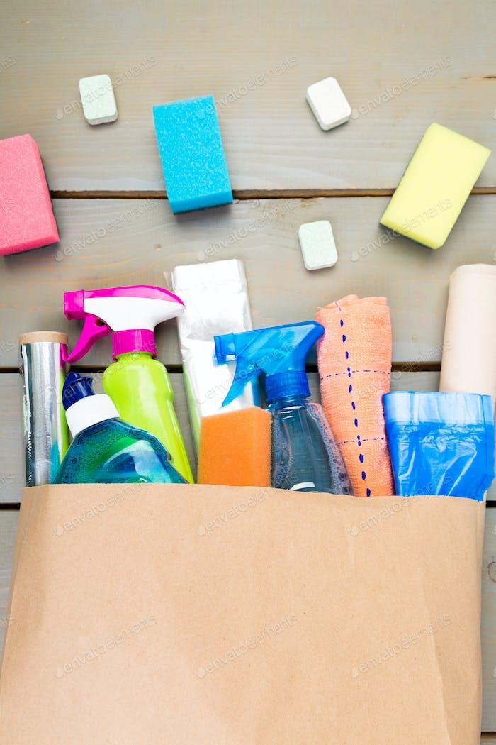 Vollpapiertasche verschiedener Hausreinigungsprodukte auf Holztisch.