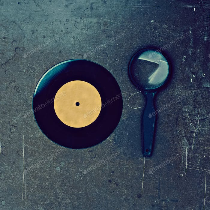 Vinyl record and magnifier on wooden table