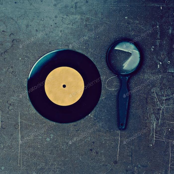 Виниловая пластинка и лупа на деревянном столе