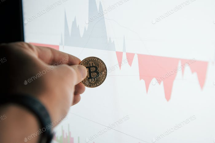 Focused photo. Man's hand holding bitcoin in modern office against monitor with graph