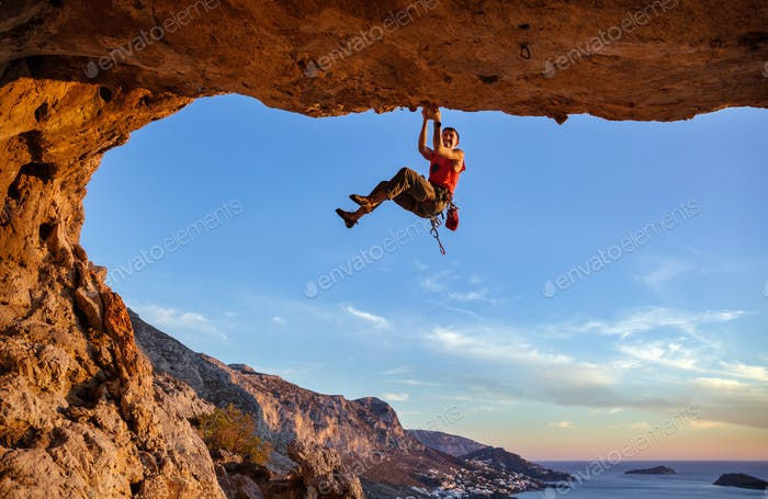 Male climber gripping on handhold while climbing in cave.