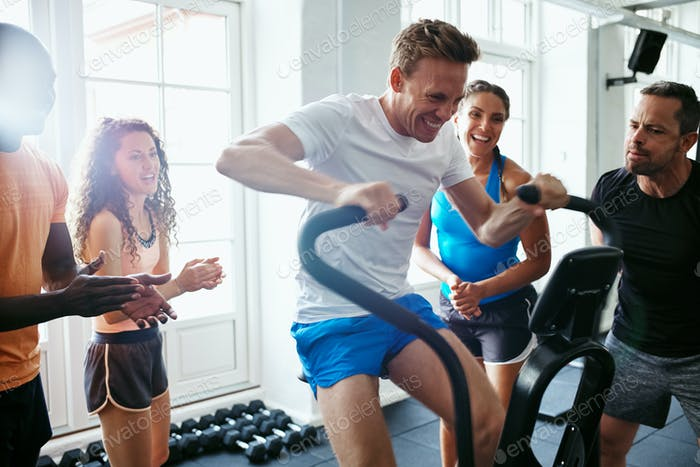 People supporting their male friend riding a gym stationary bike