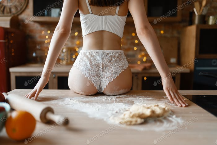 Sexy woman in lacy lingerie sitting on counter