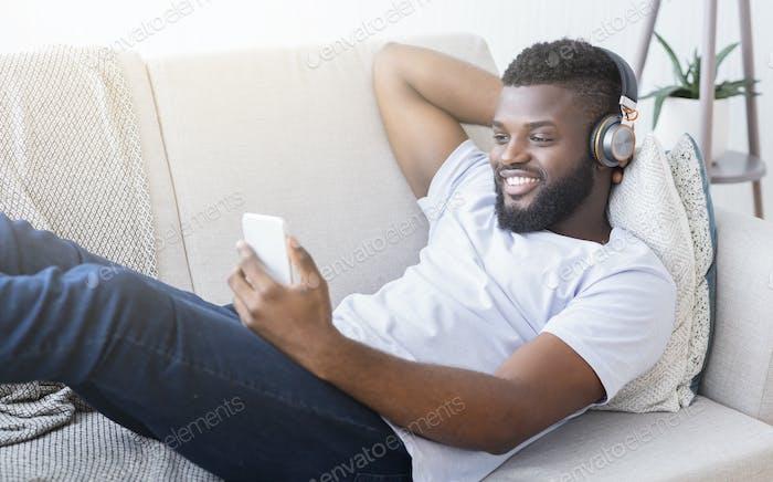 Black man in headphones watching movie on smartphone