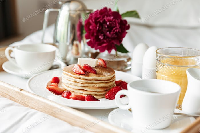 Breakfast in bed with white linen. Pancakes, boiled eggs, coffee