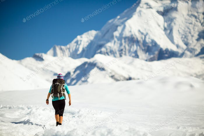 Woman walking in winter mountains