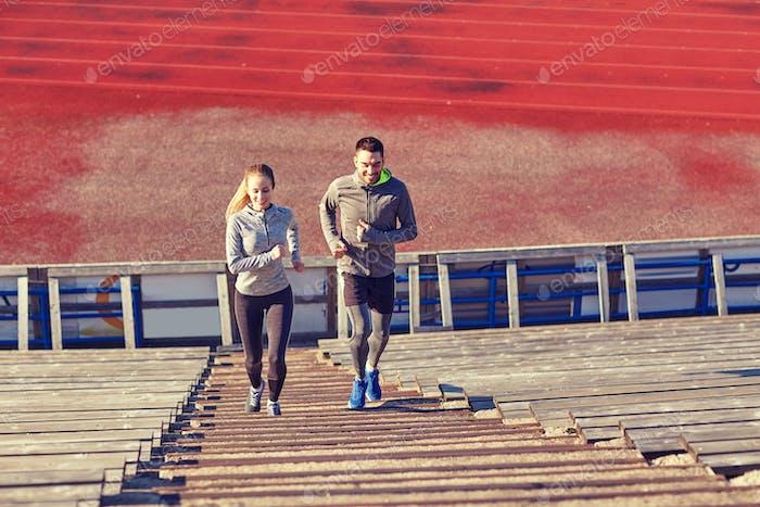 happy couple running upstairs on stadium