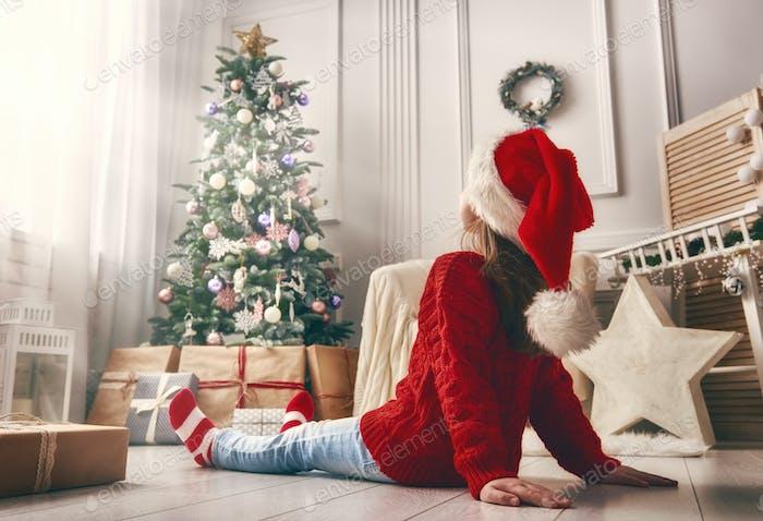Kind sitzt in der Nähe von Weihnachtsbaum drinnen