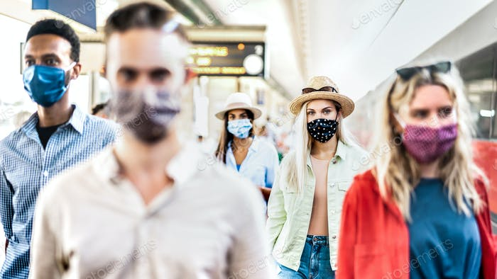 Multiracial group walking with serious face expression at railway station