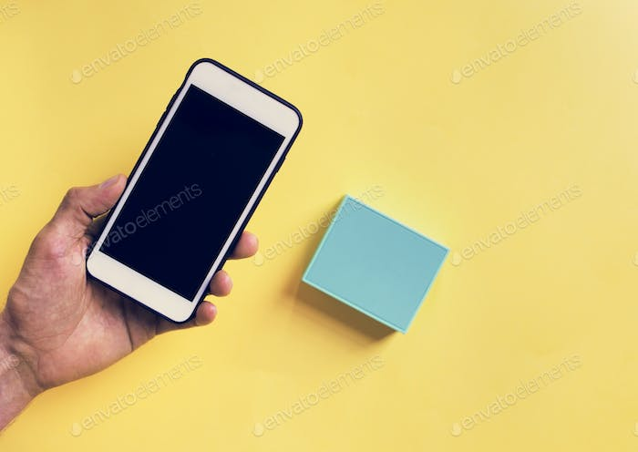 Hand holding smartphone and bluetooth speaker