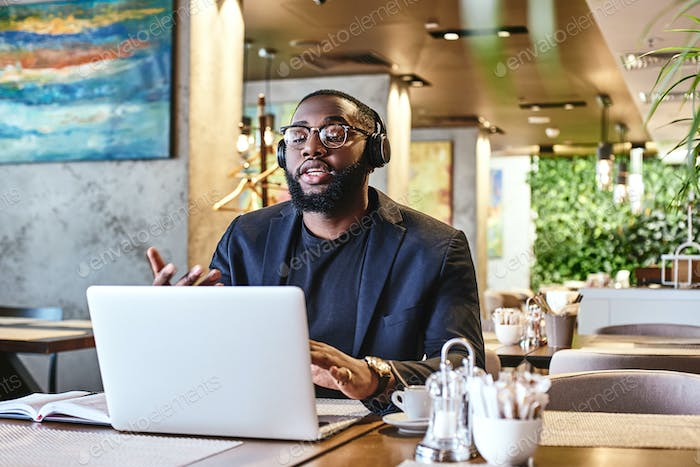 Goals are dreams with deadlines. Young businessman with headphones sitting in cafe in front of