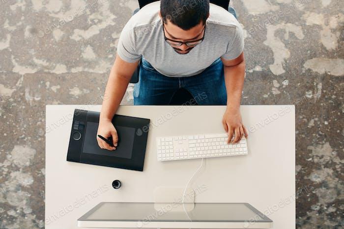 Graphic designer using digital graphics tablet and desktop