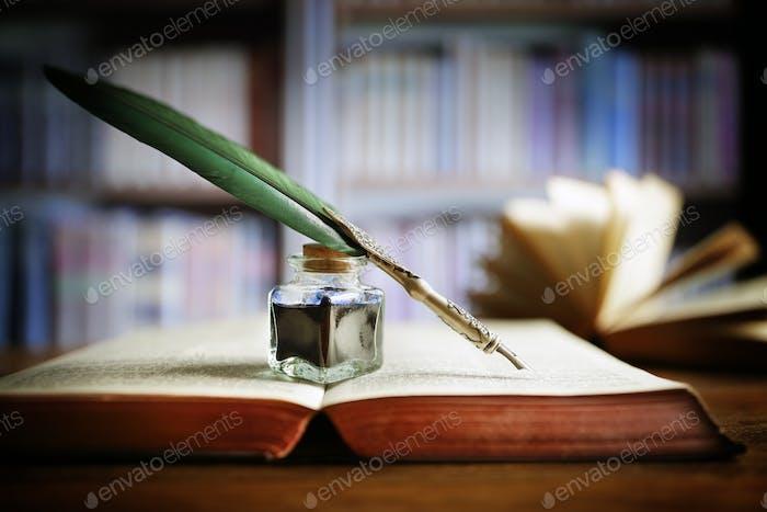 Federkiel auf einem alten Buch in einer Bibliothek
