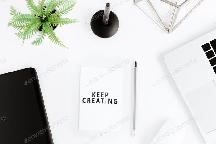 Top view of keep creating motivational quote and laptop at workplace