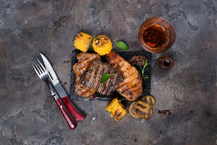 Fresh three types of grilled steak  on slate plate with herbs, juice and grilled potatoes