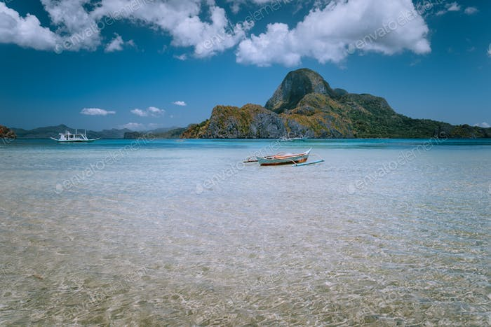Panoramic view of blue lagoon with banca boat and Cadlao Island in background. Palawan, Philippines