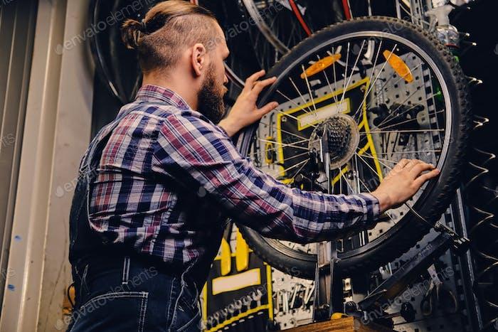 Mechanic repairing bicycle wheel tire in a workshop.