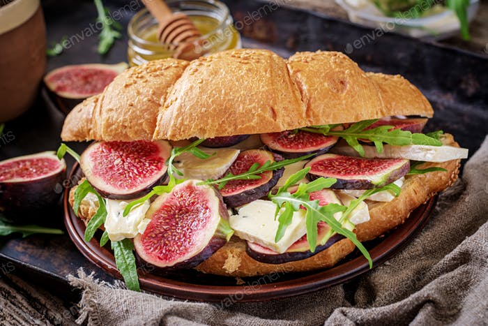 Fresh croissant sandwich with  brie cheese arugula and figs. Delicious breakfast.  Tasty food.