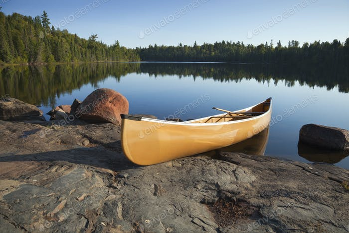 Yellow Canoe on Rocky Shore of Calm Northern Minnesota Lake