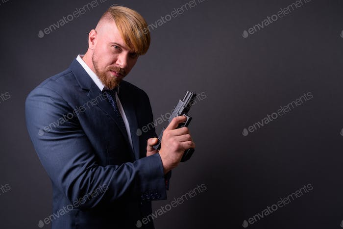 Bearded businessman with handgun against gray background