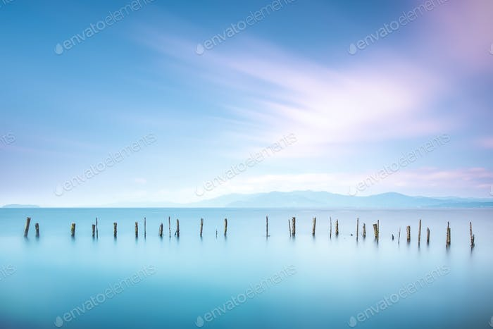 Poles and soft water on sea landscape. Long exposure.