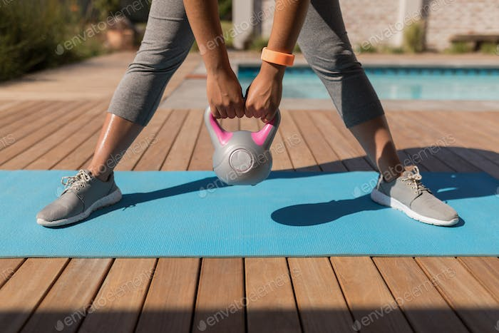 Woman exercising with kettlebell next to the swimming pool in the backyard of home on a sunny day