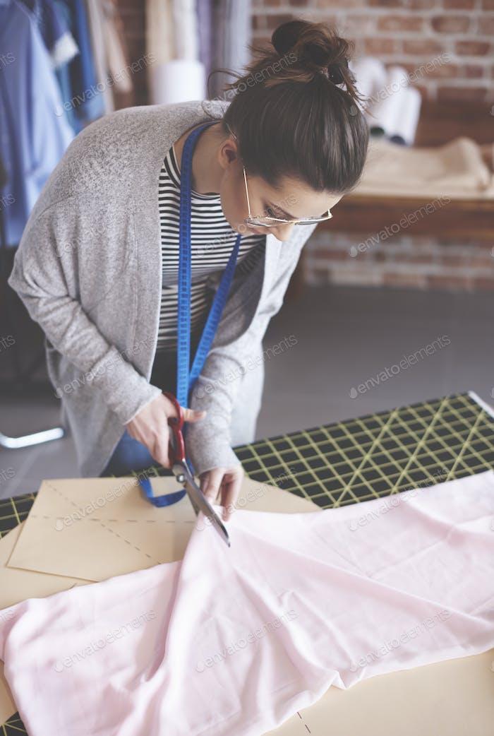 Female design professional cutting fabric
