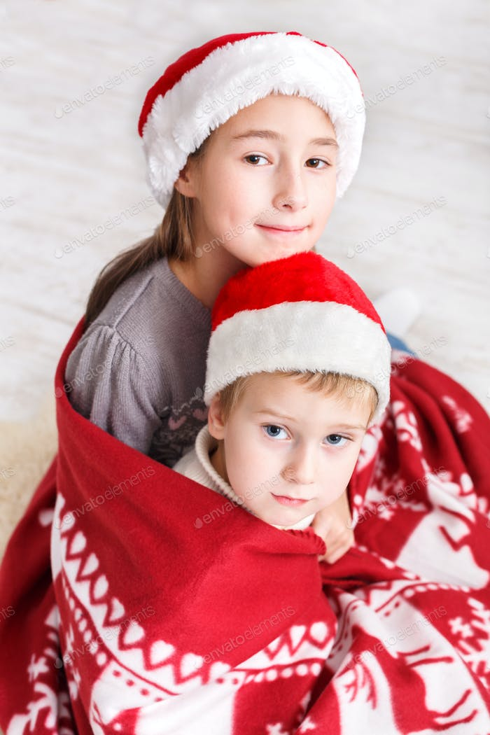 Children in santa hats near christmas tree, wait for holidays