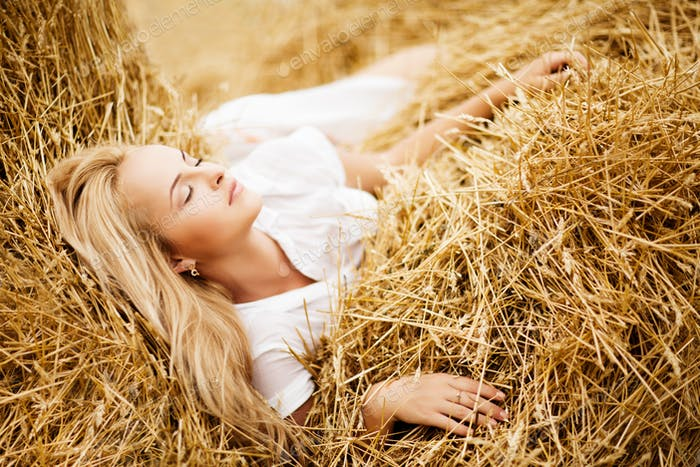 Girl with blond hair lying in hay