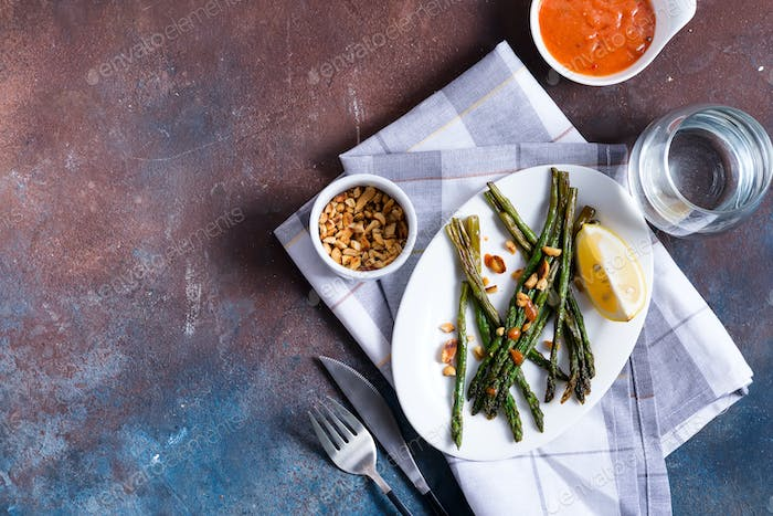 Asparagus roasted in olive oil with crushed walnuts and sauce on a dark stone background. Vegetarian