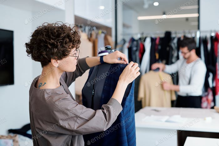 Young professional clothes designer working over unfinished dress on dummy