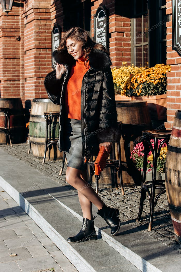 Charming slim girl dressed in skirt, orange blouse and black down jacket with fur on it walks in the