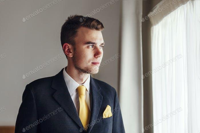 Продуманный хорошо одетый бизнесмен, глядя в гостиничный номер