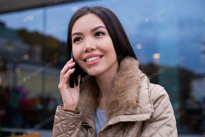 Portrait of young beautiful woman in down jacket happily talking on cellphone on city street