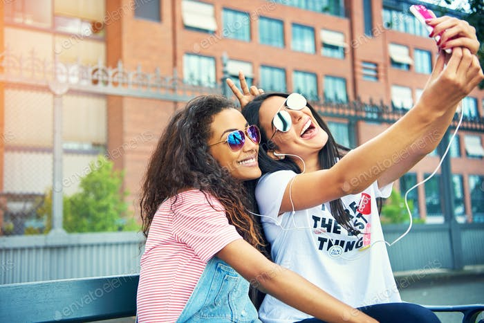 Giggling friends taking photos on bench