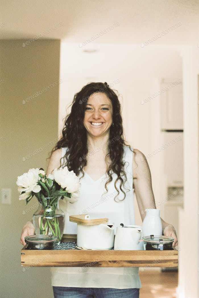 Woman carrying a tray with a teapot and a vase of white roses.