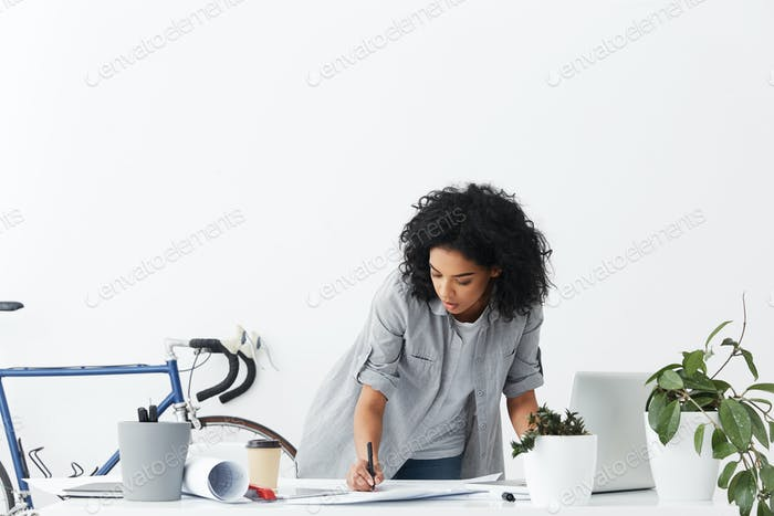 Absorbed in work. Attractive serious young African American woman engineer drawing sketch of future