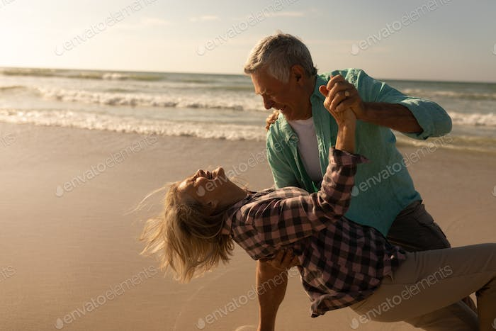 Front view of active senior couple dancing together on the beach