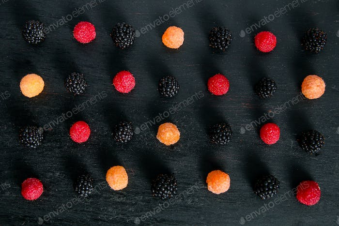 Mixed of red, black, yellow raspberries on  table. Close up.