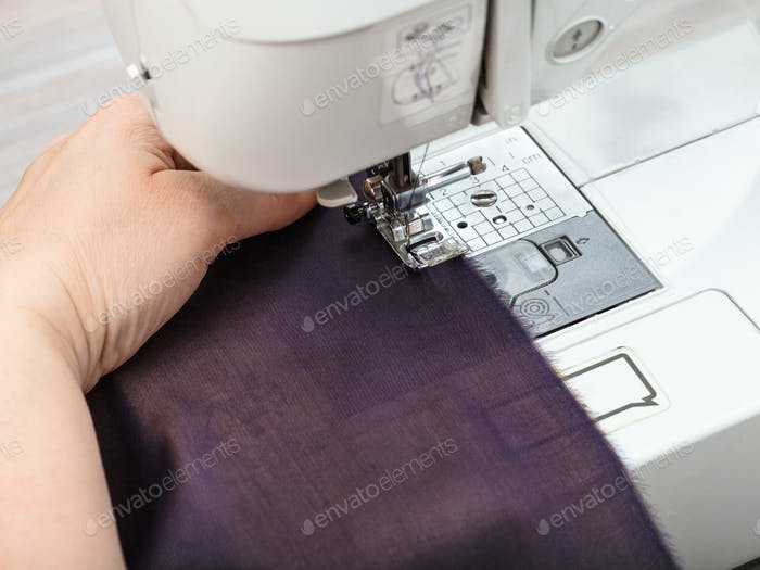 needlewoman sews strips of fabrics for patchwork