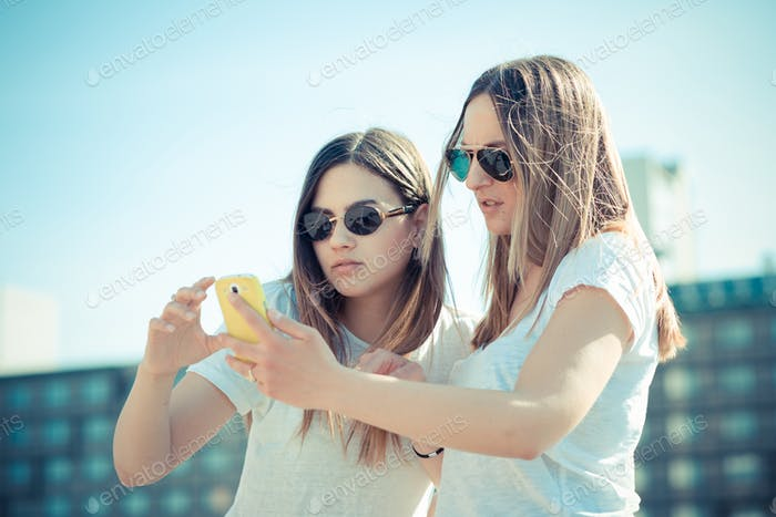 two beautiful young women using smart phone