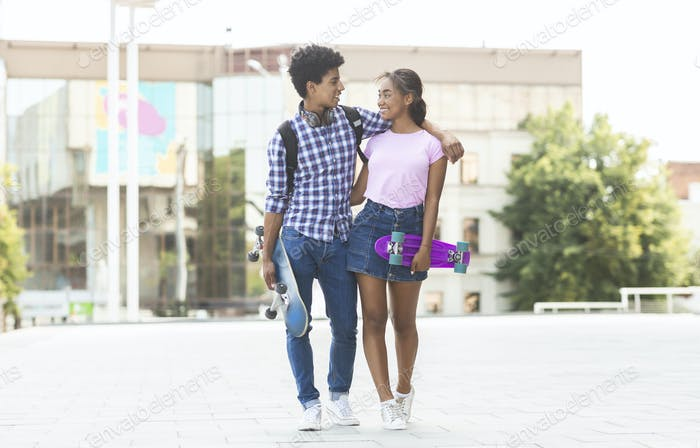 Teens dating in the city walking together outdoors