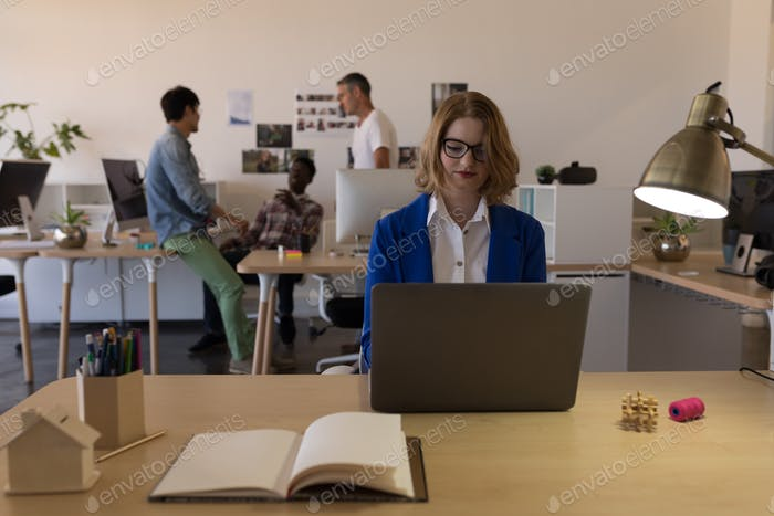 Front view of pretty Caucasian businesswoman using laptop on desk in modern office