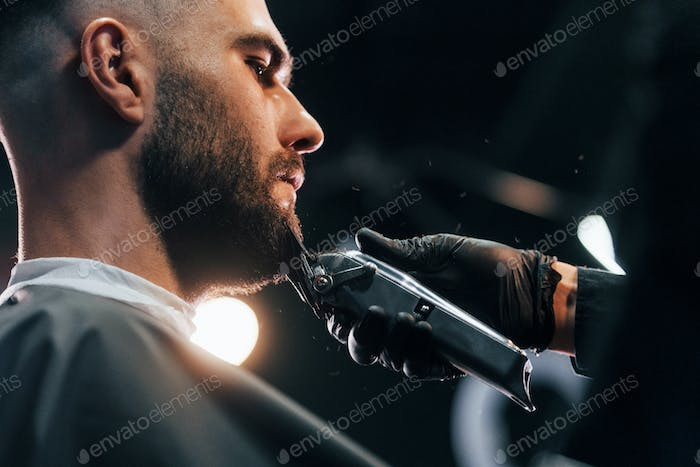 Young man with stylish hairstyle sitting and getting his beard shaved in barber shop