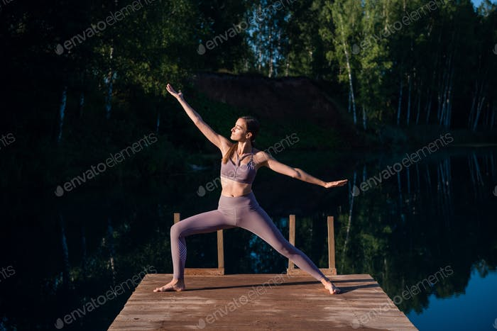 Beautiful young woman performing a spiritual yoga pose on a forest lake at sunny day, sunrise zen