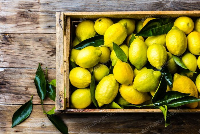 Box of lemons with fresh leaves on wooden background with copy space. Top view