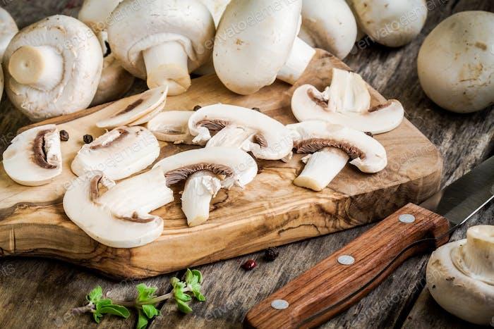 raw sliced mushrooms on a wooden cutting board