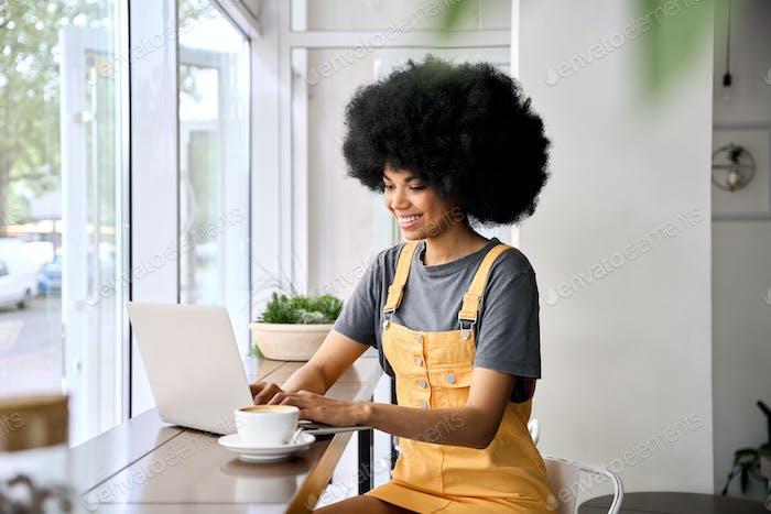 Smiling black teenage girl sitting in cafe having videocall using laptop.