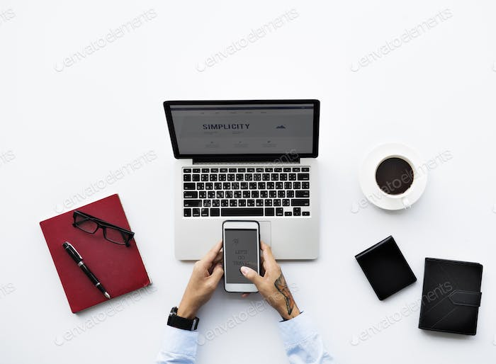 Aerial view of businessman using mobile phone with computer lapt