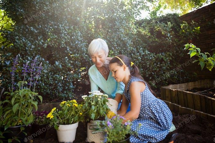 Großmutter Blick auf Mädchen Pflanzung Blumentöpfe
